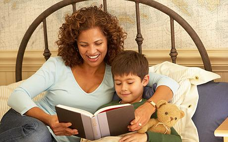 Mother reading to son (6-7) lying in bed